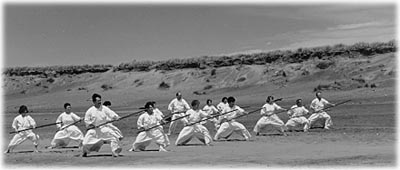 Photo of group of people practicing bojutsu on a beach